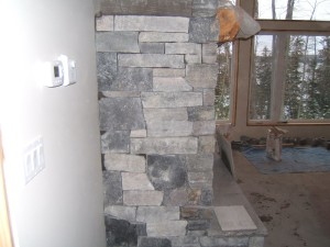 Side view of granite veneer fireplace during construction.