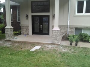 An entrance containing two pillars with cultured stone