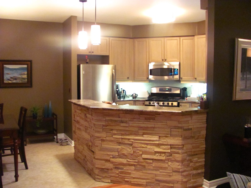 Kitchen peninsula with application of profit cultured stone.