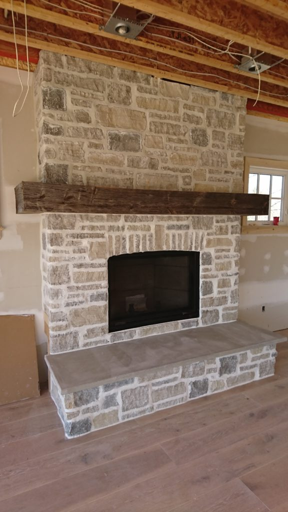 Thin cut stone veneer fireplace with vertical stone feature.