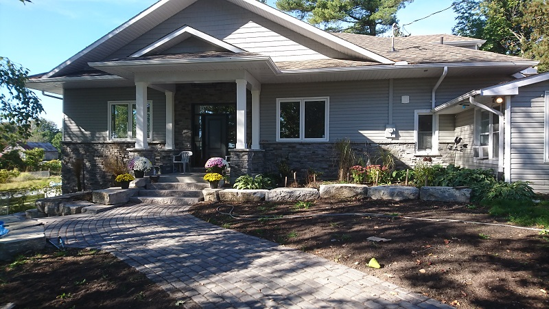 Wainscoting of stone veneer with front entrance and pillars done in same stone.