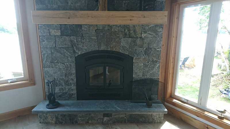 Granite veneer fireplace with feature.