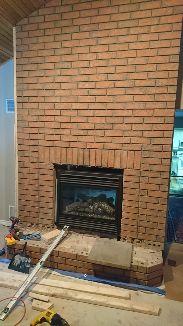 Brick fireplace before application of stone veneer over brick fireplace