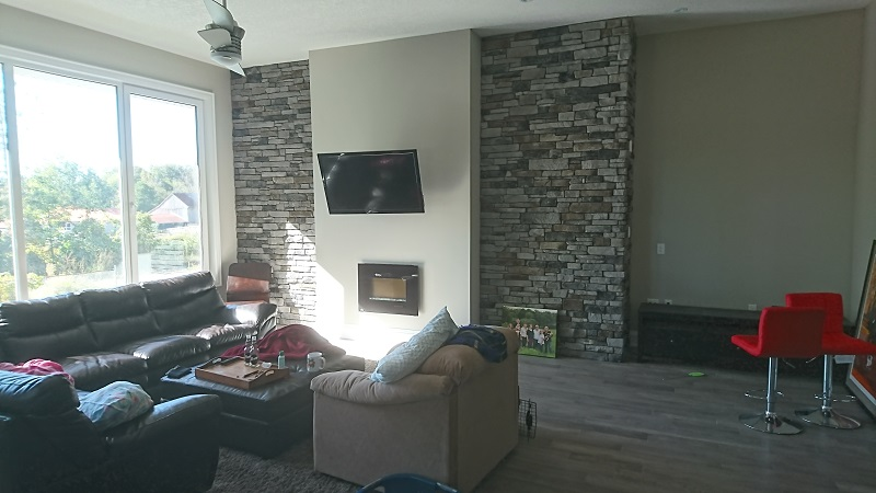 Living room featuring stone veneer accent walls.