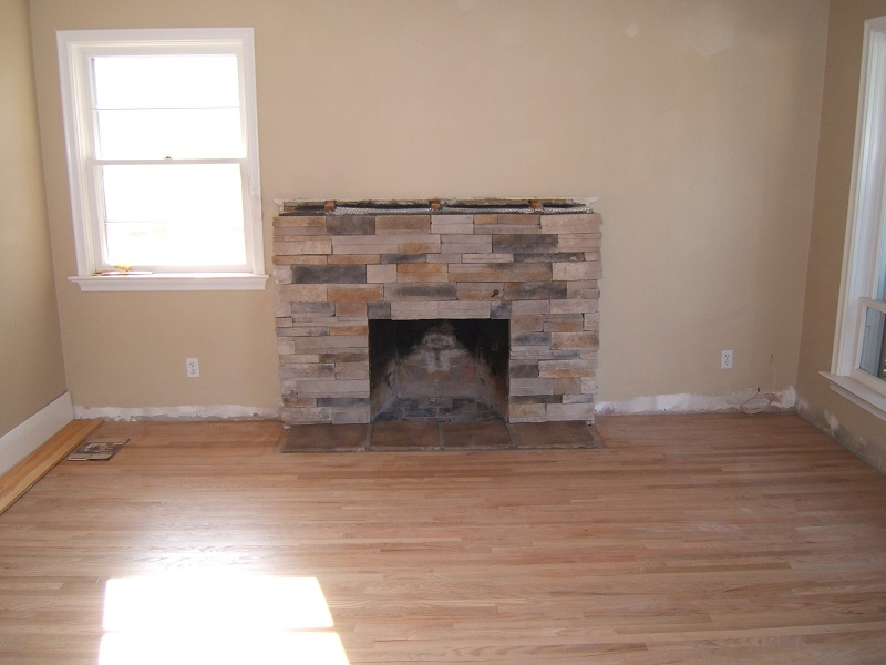 Brick fireplace resurfaced with stone veneer.