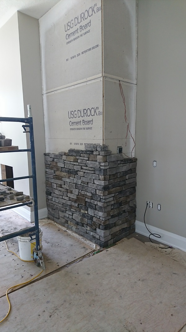 Stone veneer accent walls in process of stone being applied.