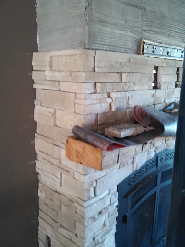 Close up of Dry Stack Stone with rustic beam on fireplace.