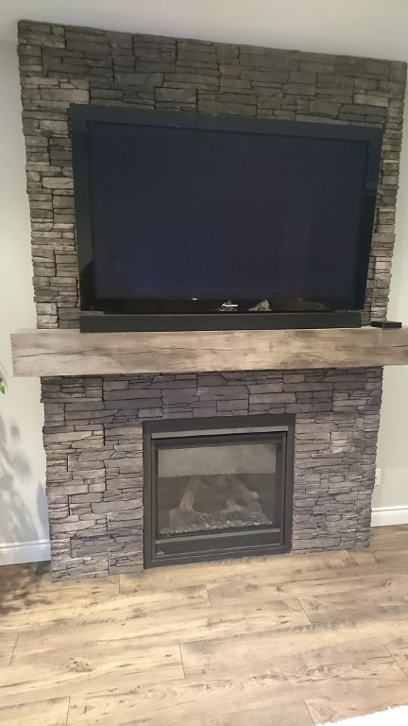 Front view of Farmledge Westchester stone veneer by Stonecraft surrounding a gas fireplace.