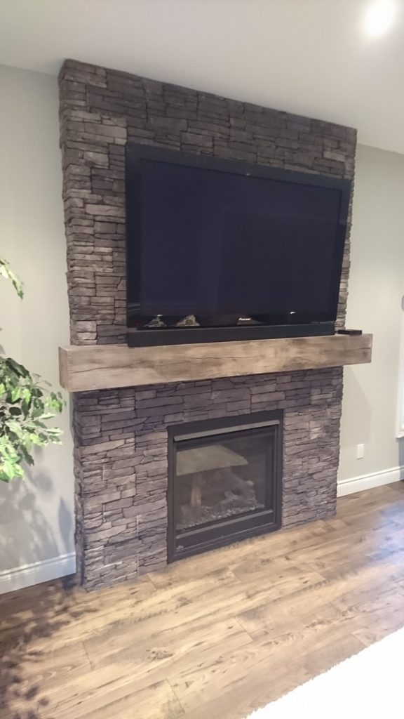 Gas fireplace with TV mounted above beam. Stone veneer is Farmledge Westchester by Stonecraft.