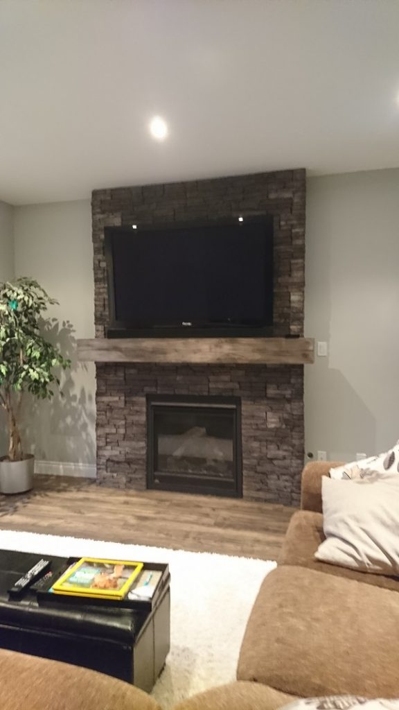 TV mounted on a stone veneer fireplace in a living room.