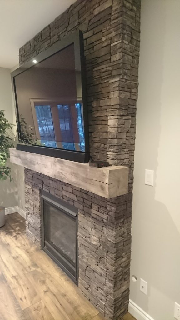 Side view of farmledge Westchester stone veneer by Stonecraft on a fireplace.