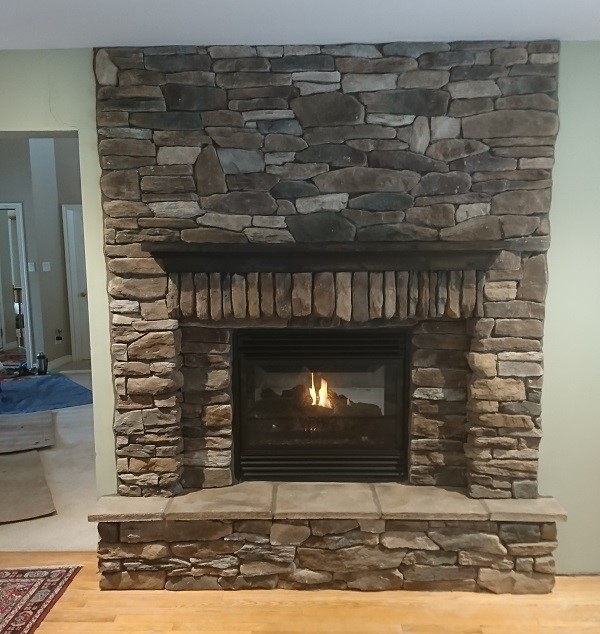 Stone veneer fireplace with dry stack pattern.