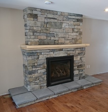 Fireplace mantle done as a two tiered shelf with upper portion of stone set back