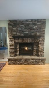 Completed accent wall with recessed gas fireplace.